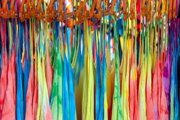 Kleurrijke zomerkleren op hangers te koop in de lokale straatmarkt in thailand, close-up
