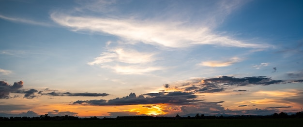Kleurrijke zonsondergang en zonsopgang met wolken. blauwe en oranje kleur van de natuur. veel witte wolken in de blauwe lucht.