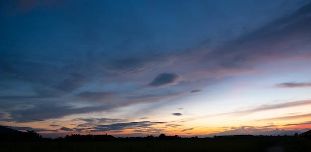 Kleurrijke zonsondergang en zonsopgang met wolken. blauwe en oranje kleur van de natuur. vele witte wolken in de blauwe lucht. het weer is vandaag duidelijk. zonsondergang in de wolken. de hemel is schemering.