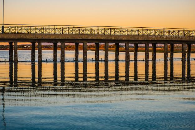 Kleurrijke zonsondergang in een brug in faro.