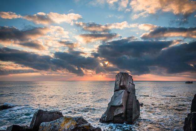 Kleurrijke zonsopgang boven rotsachtig strand.