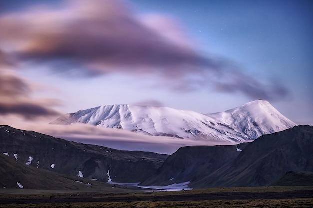 Kleurrijke zonsopgang bovenop een grote vulkaan met uitzicht over de wolken. tinten roze, paars en oranje met het silhouet van de bergen.