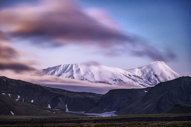 Kleurrijke zonsopgang bovenop een grote vulkaan met uitzicht over de wolken