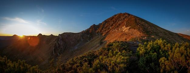 Kleurrijke zonsopgang in bergenpanorama met zongloed
