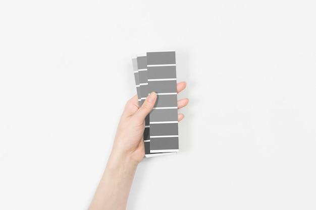 Kleurstalen met de kleur van het jaar 2021 in de hand - ultimate grey.