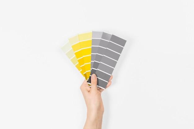 Kleurstalen met kleuren van het jaar 2021 in de hand - illuminating en ultimate grey. kleurentrendpalet.