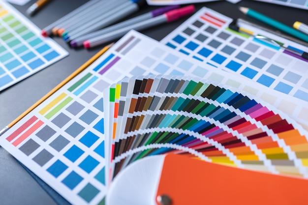 Kleurstalen van grafisch ontwerpers die op bureautafel zetten.
