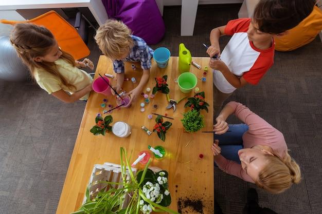Kleurtijd. leerlingen en leraar voelen zich vrolijk tijdens het kleuren van emmers voor planten tijdens de ecologieles