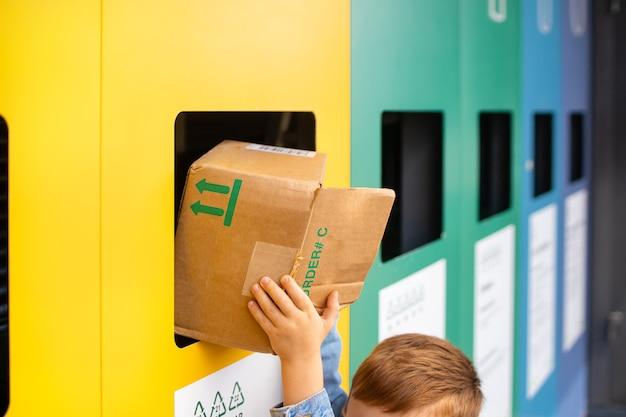 Kleuter draagt huishoudelijk gesorteerd afval voor recycling in containers voor afvalrecyclingconcept