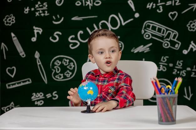 Kleuterjongen die schoolthuiswerk maakt. schooljongen met gelukkige gezichtsuitdrukking dichtbij bureau met schoollevering. opleiding. onderwijs eerst. school concept.