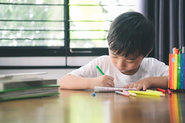 Kleuterjongen tekenen en leren thuis. onderwijs, afstandsonderwijs concept.