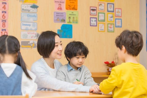 Kleuterjuf speelt met kinderen