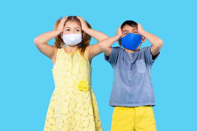 Kleuters in beschermende maskers houden hun hoofd met hun handen op een blauwe geïsoleerde achtergrond