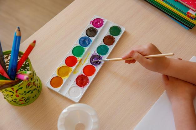 Kleuters tekenen i. baby houdt een penseel in de hand en schildert verven. het concept van de ontwikkeling van kinderen