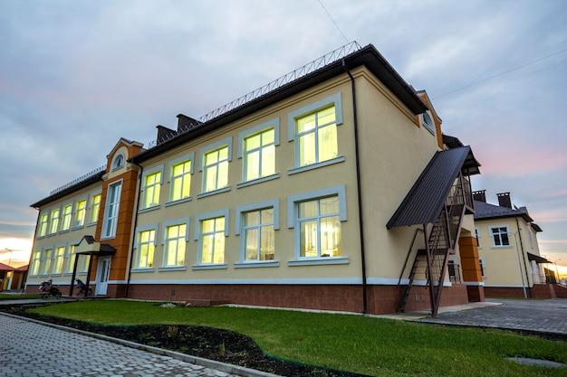 Kleuterschool voorschoolse gebouw met groen gras gazon en verharde trottoirs