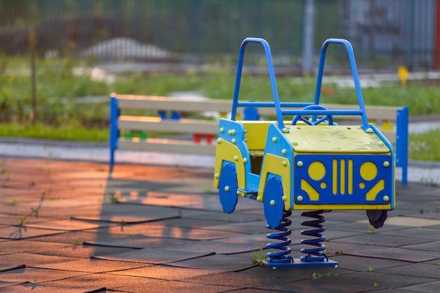 Kleuterschoolspeelplaats met heldere stuk speelgoed auto op de lente