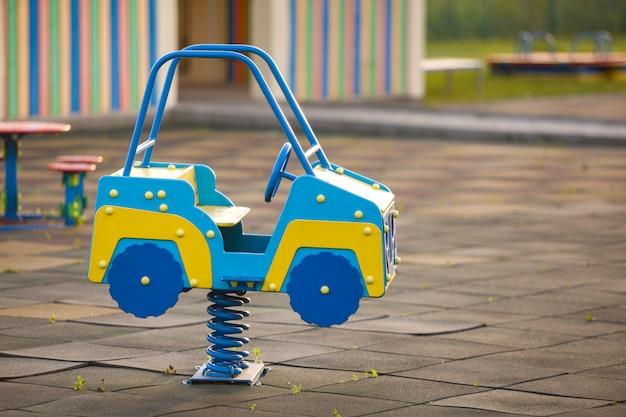 Kleuterschoolspeelplaats met heldere stuk speelgoed auto op de lente.