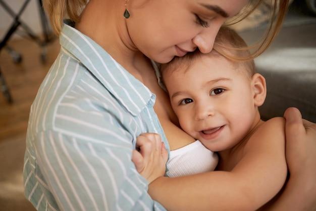 Kleutertijd, kindertijd en moederschap. liefdevolle mooie jonge moeder knuffelen thuis met haar schattige schattige zoontje, gelukkige zoete momenten doorbrengen, liefde en genegenheid tonen, kind glimlachen