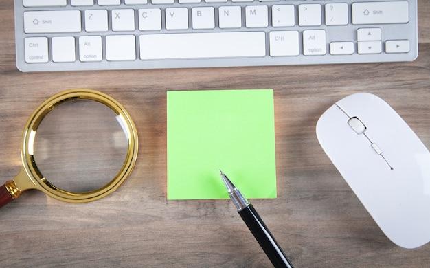 Kleverige nota met een toetsenbord en zakelijke objecten.