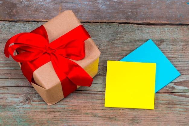 Kleverige nota met lege ruimte voor een tekst en cadeau met rood lint op houten achtergrond.