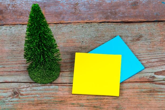 Kleverige nota met lege ruimte voor een tekst en kerstboom op houten achtergrond.
