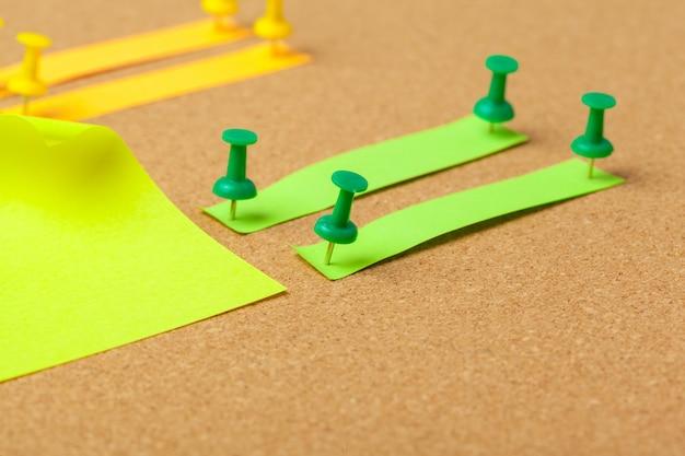 Kleverige nota's met pushpins en lege ruimte op cork achtergrond