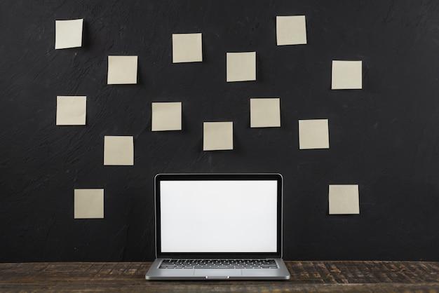 Kleverige nota stok op zwarte muur achter de witte lege het schermlaptop