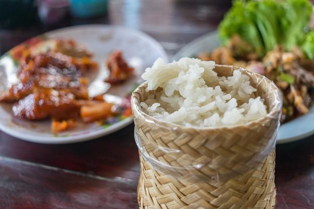 Kleverige rijst in kleverige rijstdoos met de hand gemaakt door bamboe of rijs vaag op geroosterde kip