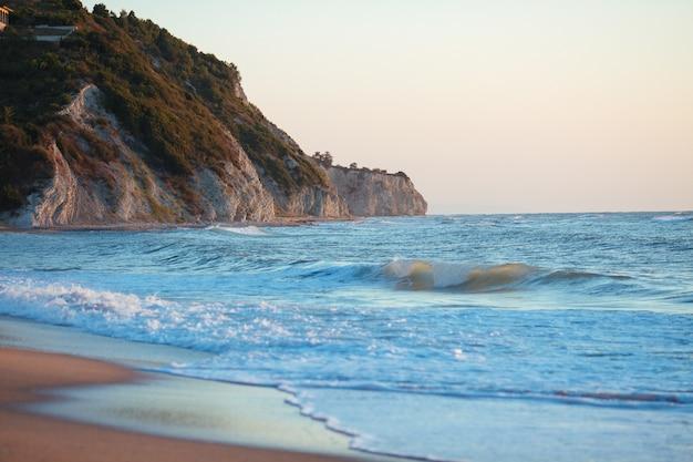 Klif en een rots in het zeestrand op een zonnige dag