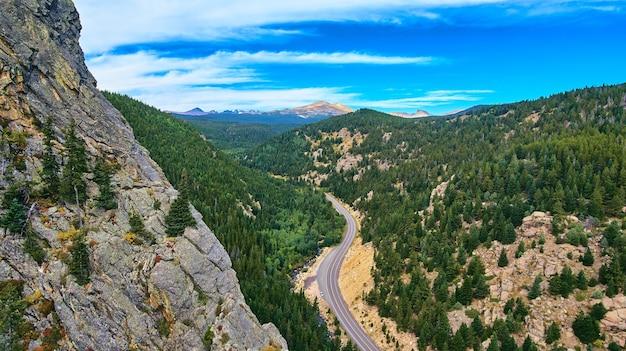 Klifberg van rotsen naast de snelweg die door pijnbomen reist