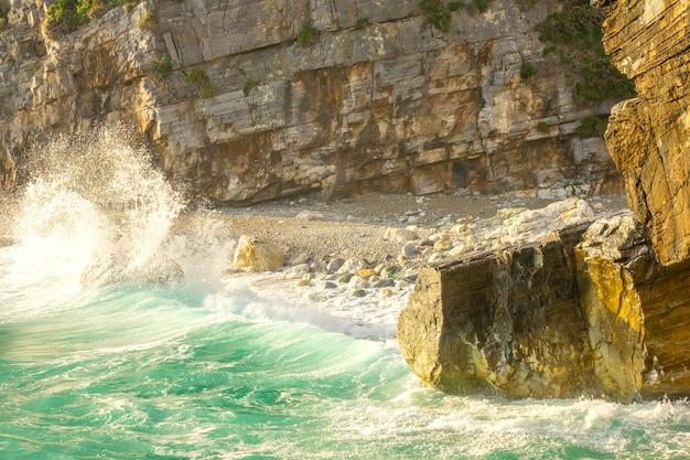 Kliffen en klein rotsachtig strand aan de kust. vroege ochtend en surfspatten