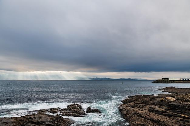 Kliffen en kleine vuurtoren op een bewolkte winterdag in portonovo in galicië, spanje, met de ingang van de ria de pontevedra op de achtergrond.