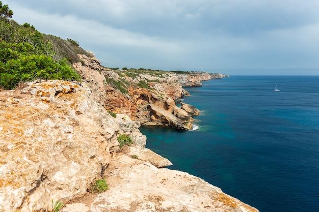 Kliffen en zeilboot op het eiland menorca
