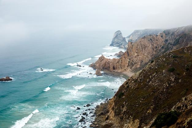 Kliffen zijn gehuld in mist in de atlantische oceaan, een natuurlijk landschap op cabo da roca in de buurt van de stad cascais, portugal. de meest westelijke kaap van het euraziatische continent.
