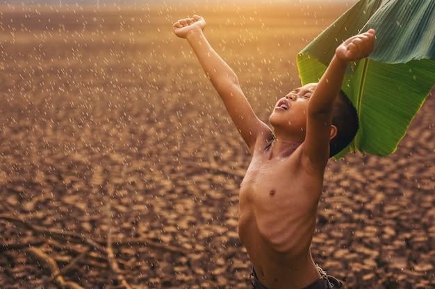 Klimaatverandering aziatische jongens genieten met eerste vallende regenseizoen op droog, gebarsten land behoud van het milieu en stop het concept van de opwarming van de aarde