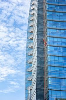 Klimmen met bergbeklimmingskoorden voor banen met risico op het reinigen van glazen kantoorgebouwen