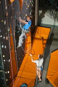 Klimmen op een indoor rotsklimmende muur, belayer staande op de grond belaying de klimmer