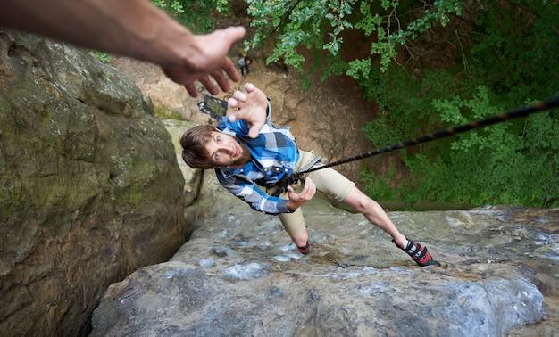 Klimmer die op touw tussen rotsen hangt en zijn hand uitstrekt. hand die in het bergbeklimmen helpt.
