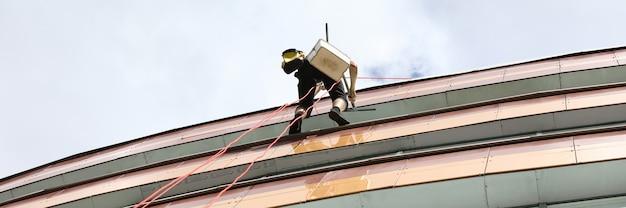 Klimmer opknoping op touwen bij het bouwen. schoonmaakdiensten voor gevels en ramen van gebouwenconcept