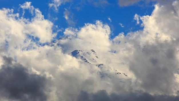 Klimmers slepen over de lenz-rotsen naar de oostelijke top van de berg elbrus, de helling met sneeuw is zichtbaar door de wolken. bergketen in de noord-kaukasus in rusland.