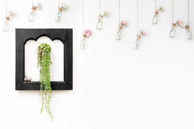 Klimop in zwart houten frame op witte muur met bloemen in hangende flessen.
