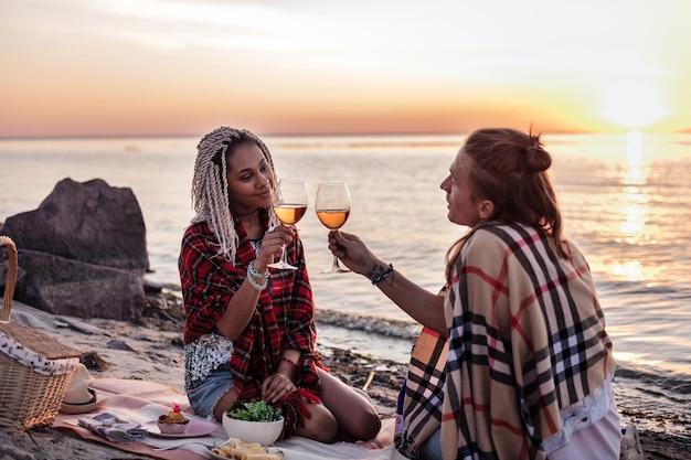 Klinkende glazen. liefdevolle stralende man en vrouw rinkelende hun glazen met wijn met avondpicknick