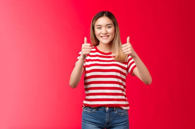 Klinkt goed heb mijn stem. vrolijk aangenaam blond aziatisch meisje steun vriend idee toon duim omhoog gebaar breed glimlachen, vrouw geven positief antwoord, eens met de goedkeuring van perfect plan, rode achtergrond