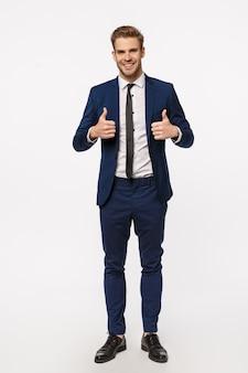 Klinkt goed, ik zit erin. verticaal schot over de volledige lengte knappe mannelijke ondernemer in klassiek elegant pak, stropdas, duimen opdagen, glimlachend goedkeuring geven, als interessant idee, witte achtergrond