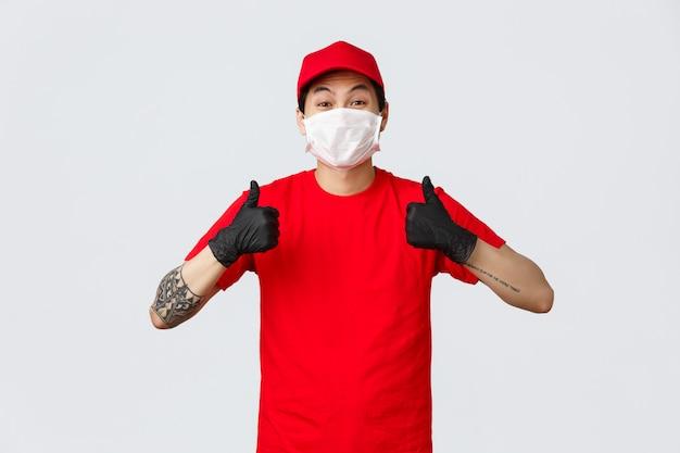 Klinkt goed. vrolijke aziatische bezorger in rode pet en t-shirt, bedrijfsuniform en medische handschoenen, beschermend masker, thumbs-up, zeg ja, keur goed of ga akkoord, beveel koeriersdienst aan