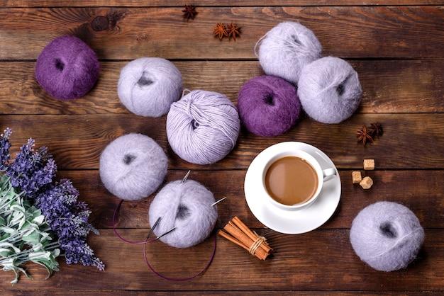Klitten van wollen draden en spaken met een kopje koffie en suiker op een houten tafel. handwerk, hobby