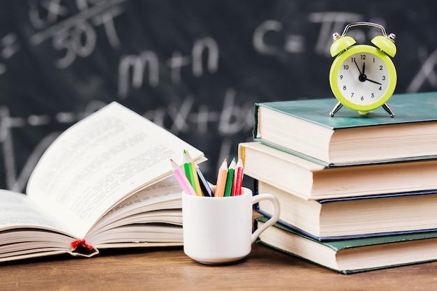 Klok bovenop leerboeken bij leraarsbureau