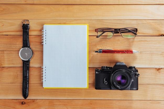 Klok, camera en notitieblok op een bruin