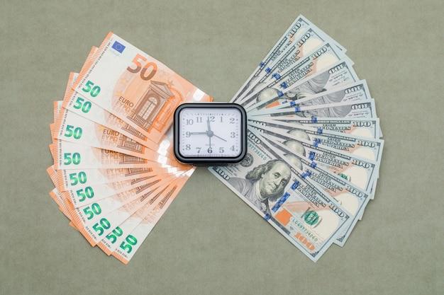 Klok, dollar en euro biljetten op groen grijze tafel.