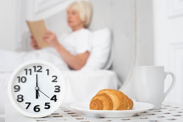 Klok en een croissant op achtergrondvrouw die een boek houdt